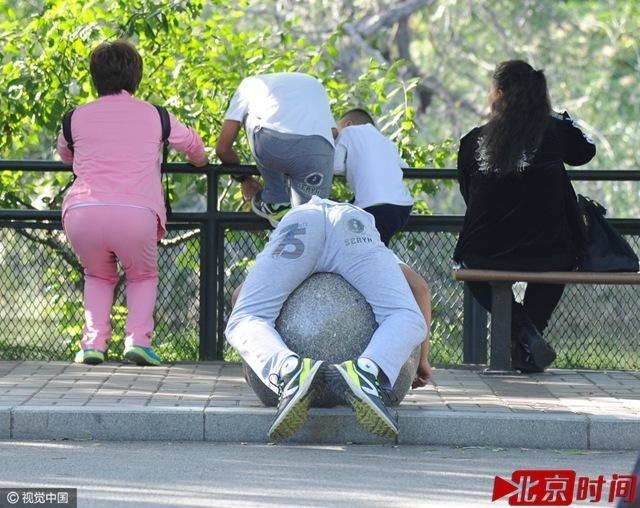 北京动物园进入游园高峰,一名男游客抱在石头球上休息.